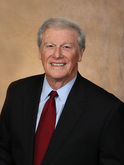 headshot of FSU's President John Thrasher smiling against gold backdrop