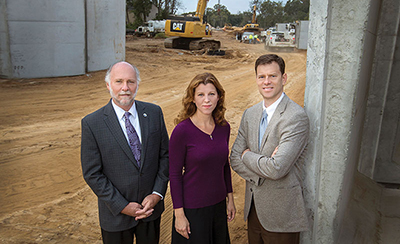 From left, Tallahassee City Commissioner Gil Ziffer, Leon County Commissioner Kristin Dozier and Kevin Graham, executive director of FSU's Real Estate Foundation, represent key partners in the multilayered Gateway District project. They were photographed at the FAMU Way Extension construction site — a key connector among the airport, the universities and downtown.
